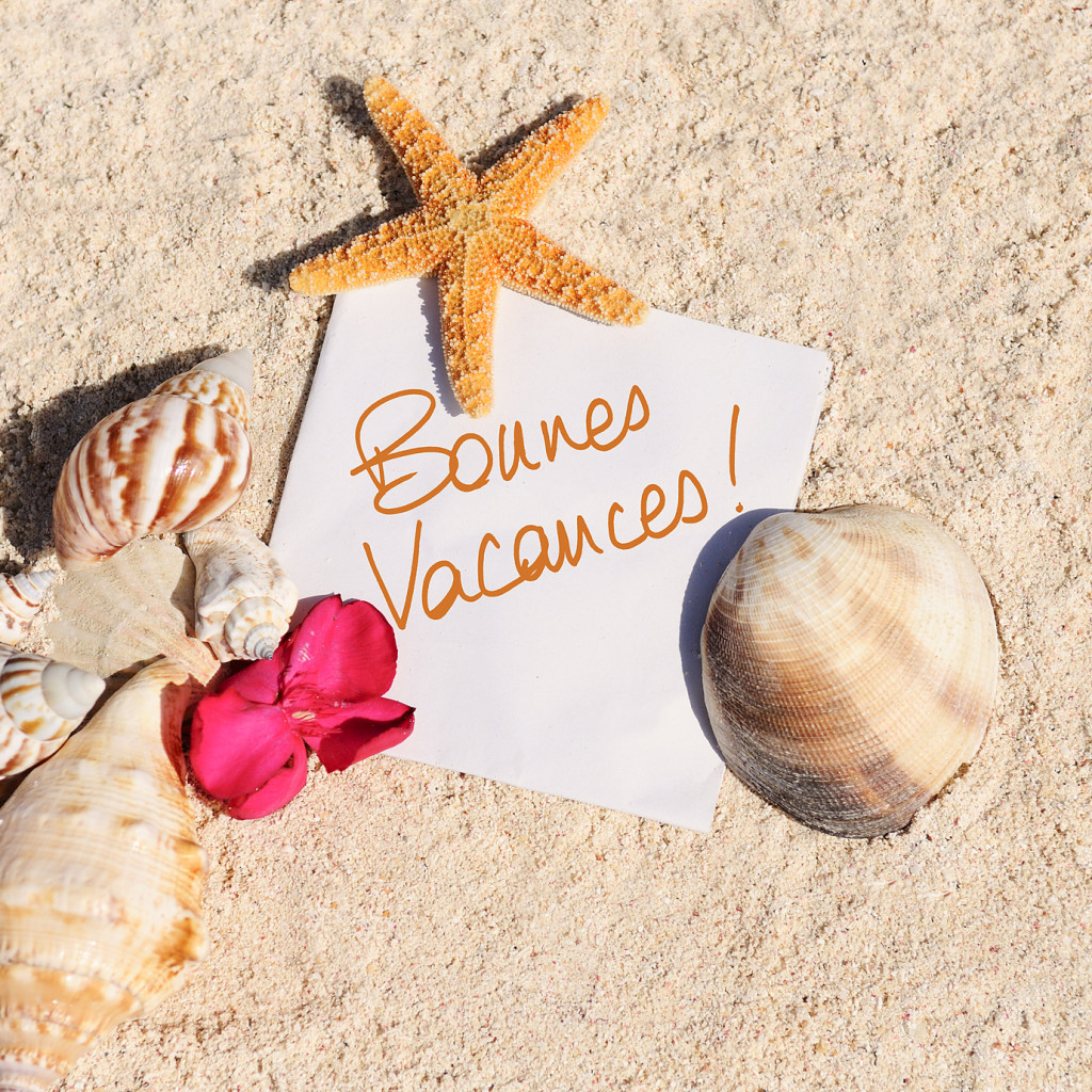 blank paper on white sand beach with starfish and shells like summer vacation background
